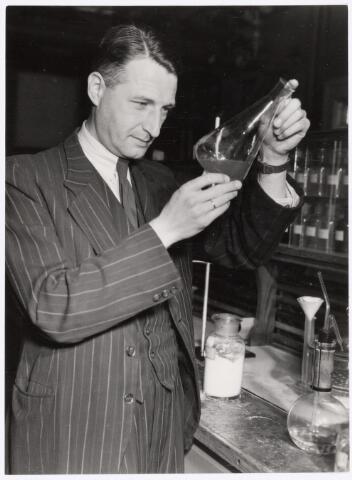 038954 - Volt. Zuid. Chemische Afdeling. Chemisch Laboratorium. Dhr. Schuring, afd. chef van deze afdelingen, bezig met een chemische analyse? Naar schatting 1940. De Voltstraat heette toen Nieuwe Goirleseweg.