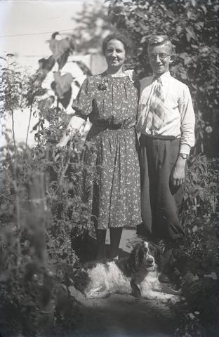 651553 - Hond. Dieren. Man en vrouwen poseren in een tuin samen met de hond. De Bont. 1914-1945.