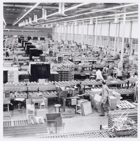 """038967 - Volt Noord. Hal N.B.Productie of fabricage afd. Deflectie Units. Overzicht van de fabricage afdeling in 1977. De zwarte """"hokjes"""" zijn monitor meetplaatsen. Hierin stonden speciaal geprepareerde televisie schermen waarop het mogelijk was de kwaliteit van de units te beoordelen. Om e.e.a. op het beeldscherm goed te kunnen zien werd dit werk in het duister gedaan. Vandaar de zwarte gordijnen er omheen."""