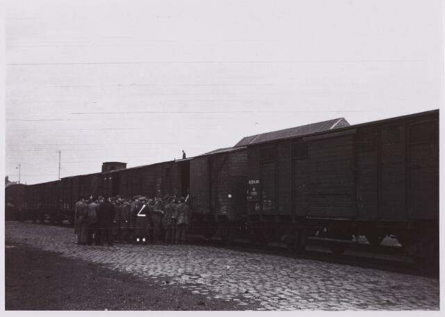 012299 - WO2 ; WOII ; Tweede Wereldoorlog. Afvoer van Duitse krijgsgevangenen bij de goederenloods van de Nedelandse Spoorwegen. Onder zware bewaking worden de voormalige bezetters een goederenwagon ingeleid voor transport naar hun vaderland