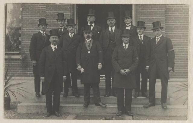 058726 - Oranjecomite, staande voor het gemeentehuis bij het regeringsjubileum vva Koningin Wilhelmina in 1923  (let op illuminatie met vetpotjes)   1e rij v.l.n.r. P.A. Verhagen, burg. D. Smits, A. Blok.  2e rij v.l.n.r. G. van Beek ? C. Beunis, Ch. Poleij, A. van Willigen, C. Nerrings, W.K. Dekkers, W. Versteeg, C. Meur.