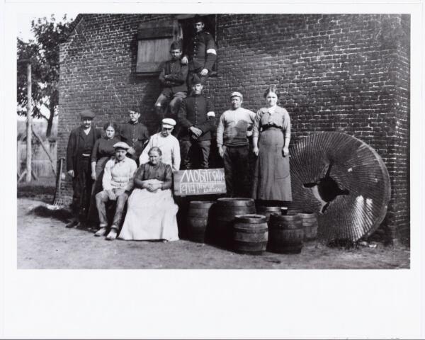 007460 - De molen aan de Elzenstraat werd gebouwd in 1861 door Jacobus Lombarts- Couwenberg. In de negentiende eeuw werd de molen ook bemalen door Cornelis Kruijssen en daarom sprak men ook wel van `Kruijssens molen´. Tijdens de Eerste Wereldoorlog, toen deze foto gemaakt werd, was de molen eigendom van de familie Mathijssen. Met het opschrift op het bord in het midden `Mobilisatie 1914, leve de kostvrouw` wordt molenaarster Adriana Smulders (Oisterwijk 1858-tilburg 1936) de weduwe van Jos Mattyijssen bedoeld. Zij zit links van het bord. Links van haar zoon Petrus (1889). Hij trouwde in Schijndel in 1917 met Maria Josephina van Dijk en volgde toen zijn moeder op als molenaar en graanhandelaar. Verder staan op deze foto twee dochters van Adriana Matthijssen- Smulders en tweede van rechts, Jan van de Rijdt. In 1963 werd de molen voor fl. 50.000 verkocht aan de gemeente door J.P.J. Mattijssen. In maart 1965 werd het bouwwerk afgebroken.