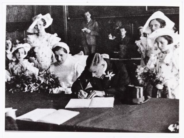 007689 - Bruiloften. Huwelijksfoto van Jan Pijnenburg (1906-1979)  met Mimi Bierens (1911-1990). Jan Pijnenburg ondertekent het huwelijksregister.