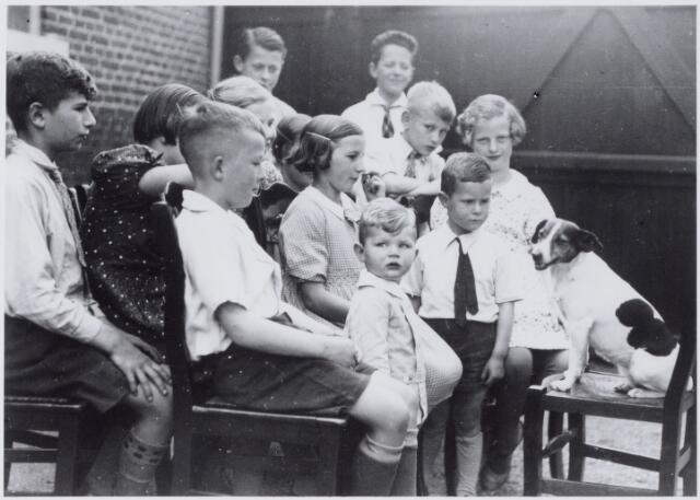 """050021 - Tilburgse kinderen met hondje op binnenplaats. Foto uit """"je Taalboek"""" van frater Victor van Nispen."""