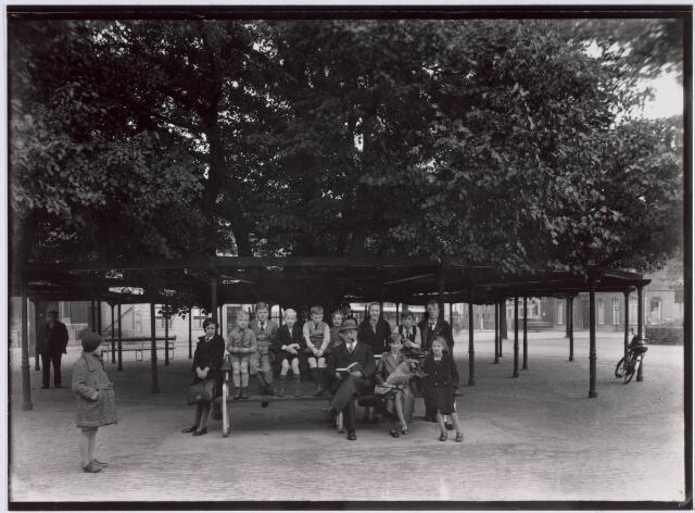 021378 - Op 9 oktober 1935 werd onder de lindeboom op de Heuvel een bank geplaatst. Dit op verzoek van duizenden inwoners. Deze foto, genomen vijf minuten na de beschikbaarstelling, toont aan dat het nieuwe stukje straatmeubilair al meteen in trek was
