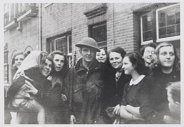 012273 - Tweede Wereldoorlog. Bevrijding. Een Schotse militair wordt in de St.-Josephstraat verwelkomd door buurtbewoners. Links van de soldaat Yvonne Vintges - Hubert, die in de Gerard van Swietenstraat woonde en op de voorgrond rechts Annie Moens, die later naar de Verenigde Staten emigreerde