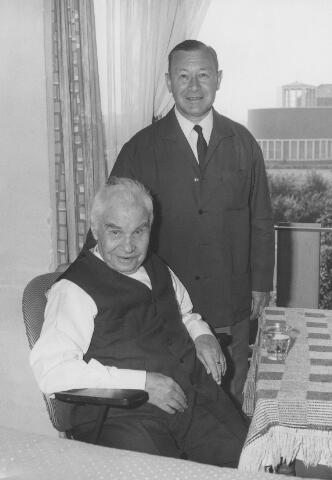 063938 - Staande, Norbert J.L.A.M. Mutsaerts directeur van wollenstoffenfabriek A. & N. Mutsaerts, op bezoek bij een oud werknemer in bejaardenhuis Vredeburcht.