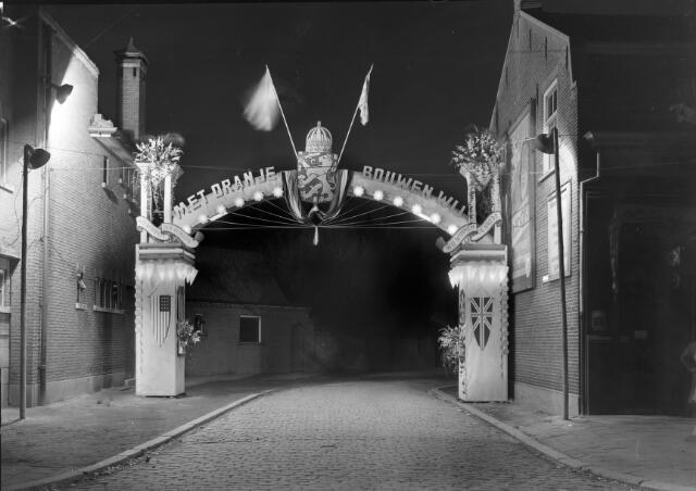 650434 - Schmidlin. Ereboog ter gelegenheid van de bevrijding, voorzien van Amerikaanse en Engelse vlaggen. De boog stond opgesteld aan het begin van de Kapelstraat, gezien vanuit de Goirkestraat.