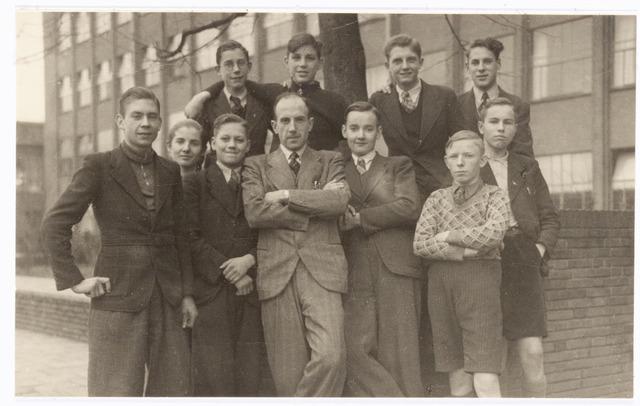 038548 - Volt. Onderwijs. Opleidingen. Leerlingen van de Volt vakliedenopleiding, studiejaren 1941-1944, waarschijnlijk bij de aanvang van de studie voor het gebouw van de Philips Bedrijfsschool te Eindhoven. Achterste rij v.l.n.r. van Beers, Moorman, van Gastel, van Beurden. Voorste rij v.l.n.r. Koolen, Robeerts, Schellekens, Hennequin (mentor?), Timmermans, de Bont, van Helvoirt. Door avondstudie hebben ook hiervan een aantal personen een hogere functie verworven.
