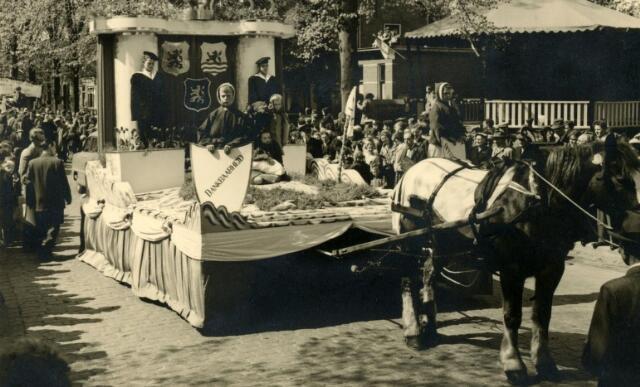 602237 - Praalwagen van buurtvereniging Kreitenmolenstraat-hoek Zeshoevenstraat, gefotografeerd in de Slimstraat, voor het gemeentehuis en de kiosk. De stoet trok door Udenhout t.g.v. de viering van de tienjarige bevrijding van Nederland. De wagen kreeg de derde prijs. De buurtvereniging had niet gekozen voor het thema bevrijding, maar voor het thema watersnoodramp, die zich voltrok in de nacht van 31 januari op 1 februari 1953. Vandaar het wapen van Zeeland en de jongens in matrozenpak. Raadhuis.