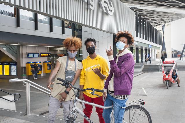 17280538 - Covid-19. Corona. Ziekten. Epidemieën. Pandemie. Openbaar vervoer. Trein. Een groepje jongeren met mondkapje op het station van Tilburg. Vanaf 1 juni is het dragen van een niet medische mondkapje verplicht in het openbaar vervoer. Daarnaast is het door alle maatregelen rustiger op het station dan normaal gesproken.