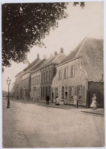 021128 - De zuidzijde van de Heuvel had al vroeg een stedelijk aanzien. Er woonden aanzienlijke lieden, zoals in de 16e eeuw de schepen en rentmeester van de adij van Tongerlo Marcelis Aertsz. van Vessem. Ernaast woonde onderpastoor tevens notaris Willem van Gemonde. De op deze foto van omstreeks 1900 voorkomende panden stammen deels nog uit de 18e eeuw. Het huis rechts, met de brede klokgevel, was de bakkerij van de weduwe Knegtel, later garage Knegtel en daarna winkelcentrum Heuvelpoort