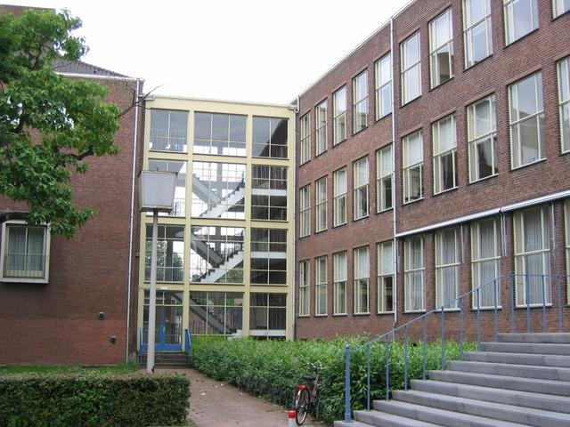 655574 - Monumentenzorg. Monument. Het Paulus Lyceum. Deze school was een afsplitsing van het Sint Oldulphus Lyceum en in september 1954 begonnen de eerste lessen.  In opdracht van de Canisiusstichting Tilburg werd in 1957 begonnen met de bouw van een nieuwe school op de hoek van de Ringbaan-West en de Wandelboslaan. In 1960 werd het complex, een ontwerp van Kees de Bever, ingezegend door mgr. Wilhelmus Marinus Bekkers. De school kreeg in 1995 een nieuwe vleugel aan de kant van de Reitse Hoevenstraat.