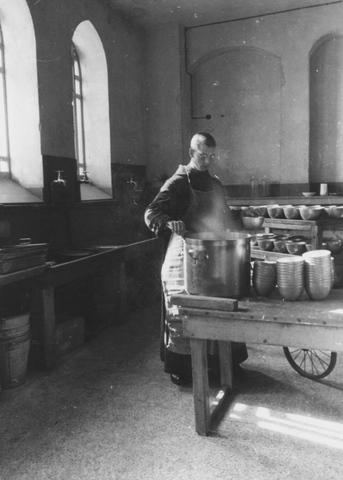 105295 - Monnikenleven De jonge frère Benoît (broeder Benedictus) vult in de keuken de soepkoppen voor de maaltijd van de monniken. Kloosters. Sint Paulusabdij.
