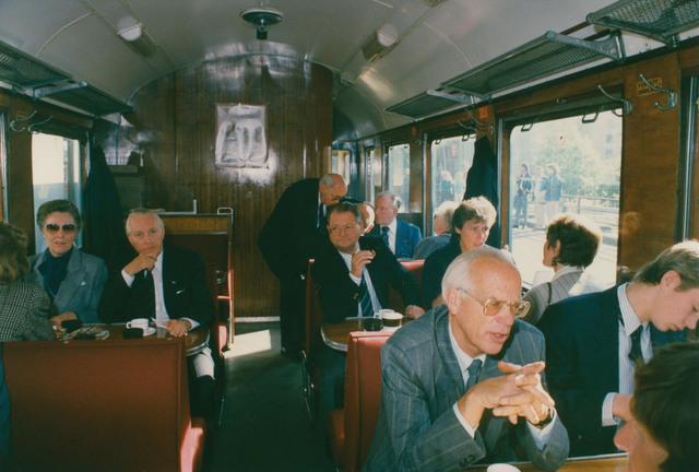 651287 - Tilburg, 125 jaar stad aan het spoor. Manifestatie. Om half elf vertrekt de stoomtrein naar Tilburg. De eerste wagon achter de locomotief is het restauratie-bagagerijtuig. Daarin zitten de leden van het Committe van Aanbeveling en van het Erecommittee