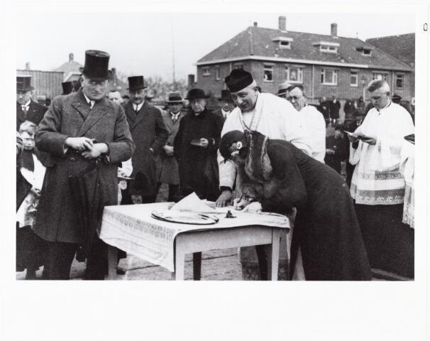 010056 - op 9 mei 1932 werd de eerste steen gelegd voor de nieuwe parochiekerk van het Allerheiligste Sacrament aan de Ringbaan-Oost. 'Juffrouw Cuners van Oorschot ondertekent den Bul' Links van haar bouwpastoor J.W.A. van Oorschot, daarnaast deken J. Sanders pastoor van de Noordhoek.