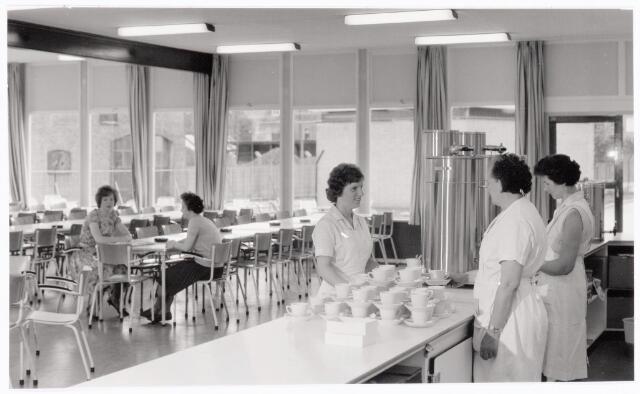 """038673 - Volt. Zuid. Kantines. Bedrijfsrestaurants. De z.g.n. buiten kantine aan de Radiostraat. In gebruik genomen in 1965. Gebouw AM. Volt zat toen op de top van het personeelsbestand ooit en noord was pas sinds kort in ontwikkeling zodat deze """"noodkantine"""" bittere noodzaak was. Deze kantine heeft nooit de naam bedrijfsrestaurant gehad. Nog in 2003, Volt bestond al niet meer, werd deze kantine gebruikt voor Bingo avonden t.b.v. de oud Volt voetbal-vereniging T.A.C. De tweede dame van rechts is Mietje van Gestel, uiterst rechts Miet v.d. Berg. Voor de balie Cor Lips. Aan tafel links Ietje Jansen en rechts Tonnie Santegoeds."""
