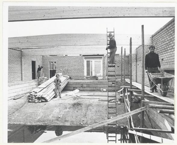 90535 - Made en Drimmelen. De Madese postbode Piet van Geloof(r) bouwt samen met bekenden een overdekt zwembad in de Wilhelminastraat in Made. Geheel links achter Ria Broeders zijn vrouw, midden bij het hout Nolleke Broeders, zijn schoonvader. De man op de ladder is niet bekend.