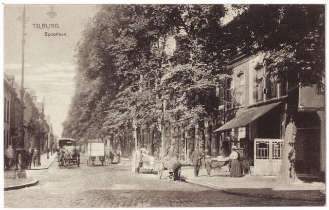 002128 - Spoorlaan gezien vanaf de Heuvel. De eerste twee panden rechts hadden voor 1910 de huisnummers Spoorlaan N282 en N281. In 1910 kregen deze twee panden de huisnummers Heuvel 4 en 5. Pas bij het derde huis begon dus de Spoorlaan. Het hoekpand nr. 4 en het om de hoek gelegen pand Heuvel nr. 3, toen N 283, werd in 1890 betrokken door Henri de Leuw. Hij was kleermaker en verhuurder van rouwmantels en hij begon in pand nr. 4 een 'herbergaffaire'. Het pand kreeg de naam café 'Marktzicht. Rond 1900 was G.L. Poos er herbergier. De Leuw was inmiddels verhuisd naar het pand Heuvel nr. 5, waar hij op 28 mei 1920 overleed. Zijn weduwe, Jacoba Johanna van Spaandonk, bleef op nr. 5 woonachtig. 'Marktzicht' werd later bewoond door de gezusters Dusée. Een van hen, Maria Anna Catharina Dusée, geboren te Tilburg in 1885, trouwde in 1913 met Adrianus Judocus Jacobus Gaillard geboren te Tilburg in 1886. Hierna stond het pand bekend als café Gaillard. Voor het café een hondenkar en een handkar. In september 1960 is café Gaillard gesloopt iv.m. de aanleg van het hoogspoor. In een van de eerste panden rechts was eind jaren `50 - beginjaren `60 van de vorige eeuw advocatenkantoor De Voort & Pessers gevestigd