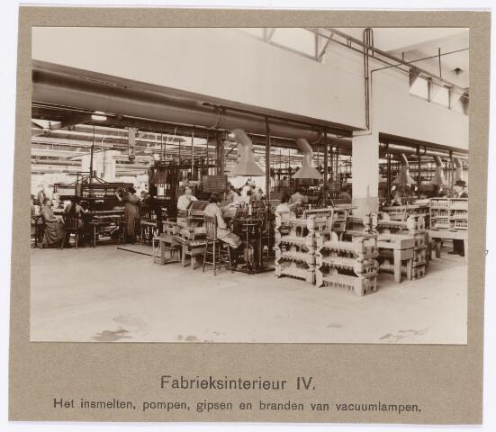 039072 - Volt. Zuid. Productie, fabricage van lampen in 1925. Hier werden de lampen ingesmolten, vacuum gepompt, van gips voorzien en gebrand. Waarschijnlijk wordt daarmee bedoeld dat de fitting aan het glas werd gebakken. De foto is genomen vanuit gebouw B (onder de kantine aan de Voltstraat) en gaat over in de shedbouw C. Voltstraat was vroeger Nieuwe Goirleseweg.
