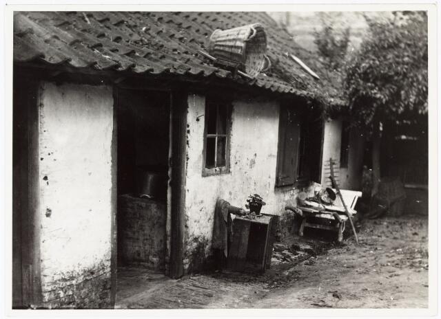 008499 - Achterzijde van een huisje met kruiwagen en mand op het dak, gefotografeerd door Henri Berssenbrugge (1873-1959) begin 1900.