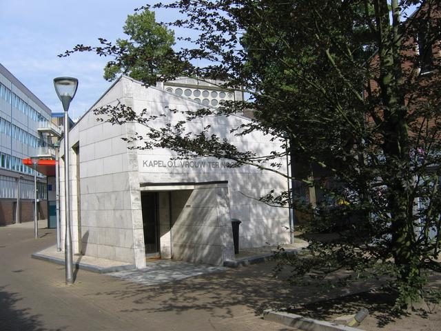 655554 - Monumentenzorg. Monument. Het pleintje, met inbegrip van de noordelijke en oostelijke toegang, gelegen ten westen van de Oude Markt en ten zuiden van de Heuvelstraat, de Kapelhof met de kapel van O.L. Vrouw ter Nood. De kapel werd ingezegend op 7 juni 1964 door mgr. BekkersArchitect en was de architect Jos. Schijvens, terwijl het ontwerp van de glas-in-betonmotieven werd vervaardigd door Daan Wildschut. Kees Mandos calligrafeerde het herdenkingsboek met de namen van de in de oorlog omgekomen stadgenoten