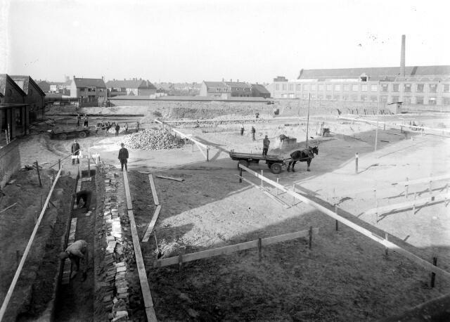 650463 - Schmidlin. Aannemer Smulders bouwt de nieuwe fabriek van de firma Thomas de Beer, fabrikant van wollen stoffen, gelegen aan het Wilhelminapark en de Kuiperstraat.
