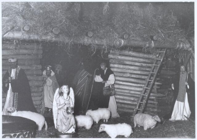 019679 - Beeldengroep van de kerststal in de Goirkese kerk. Links op de voorgrond een knikengeltje dat met haar hoofd bewoog als er een munstuk in het potje werd gestopt