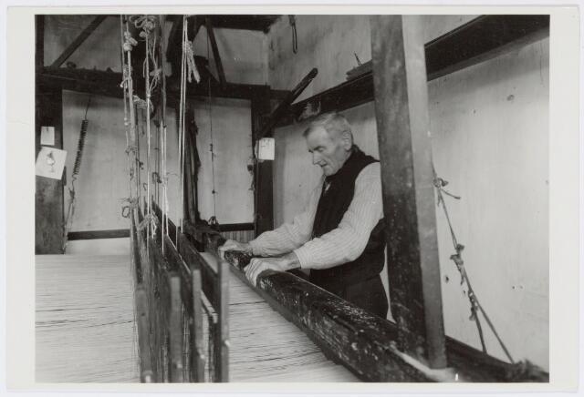 037460 - Textielnijverheid.  Thuiswever Frans van Geloven aan zijn getouw. Hij woonde in de Tongerlose Hoefstraat en was de laatste praktiserende thuiswever in Tilburg.