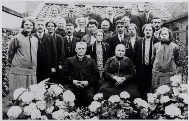 045865 - Jan Adams en Trien Stockermans vierden in 1928 aan de Kerkstraat hun veertigjarig huwelijksfeest. Zij trouwden in Goirle op 11 april 1888. Jan was meesterkecht bij de firma Van Besouw. Trien dreef een winkeltje in rookartikelen en ansichtkaarten. Op de voorgrond Jan Adams, geboren te Bladel op 20 oktober 1861 en overleden te Goirle op 4 november 1929, en zijn vrouw Anna Catharina (Trien) Stockermans, geboren te Udenhout op 17 juli 1866. Op de volgende rij hun kinderen; v.l.n.r. Cornelia Adriana Maria (Cor) geboren te Goirle op 23 mei 1903, aldaar overleden op 16 maart 1980. Zij trouwde met Adrianus W.C. Luijten. Haar broer Gerardus Maria Johannes Adams, geboren te Goirle op 15 augustus 1890, overleden op 31 mei 1968, zijn vrouw Maria Elisabeth Broers, geboren te Goirle op19 januari 1892, overleden te Tilburg op 6 oktober 1963, Martinus Petrus Adams, geboren te Goirle op 22 mei 1889, aldaar overleden op 19 juli 1966, zijn vrouw Antonia Maria Josephina Spapens, geboren te Goirle op 3 augustus 1888, overleden te Goirle op 28 mei 1959, rechts voor haar Maria Hendrica Adams, geboren te Goirle op 8 januari 1892 en aldaar overleden op 18 maart 1979. Zij bleef ongehuwd. Vervolgens Wilhelmus van Son, geboren te Drunen op 10 juli 1903, overleden te Goirle op 4 december 1972, zijn vrouw Petronella Antonia Martina Adams, geboren te Goirle op 1 januari 1900, overleden te Tilburg op 21 augustus 1932, Bernardina Petronella Maria Adams, geboren te Goirle op 3 januari 1894, overleden te Tilburg op 16 januari 1973. Achter haar, haar man Hendrikus Cornelis Witters, geboren te Goirle op 13 januari 1896, overleden te Tilburg op 2 augustus 1874, en Johanna Maria Adams, geboren te Goirle op 24 juli 1904 en overleden te Tilburg op 10 februari 1997. Zij trouwde met Theodorus A.H. Koolen. De oudere vrouw met muts op de volgende rij is een schoonzus van Trien Stockermans, Johanna Maria van Vugt, weduwe van Johannes Cornelis Stockermans, geboren te Moergestel op 6 november 1863 en ove