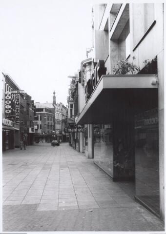 021673 - Heuvelstraat ter hoogte van modezaak Gimbrère (rechts). Links de vestiging van C. Jamin en daarnaast bonthandel Dora van de Ven. Ter hoogte van de auto in het midden de kruising met de Willem II-straat. Op de achtergrond de toren van de Heikese kerk