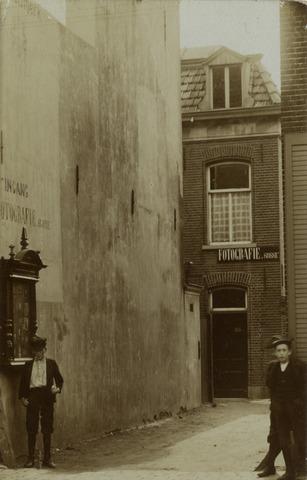 650405 - Schmidlin. 11 juli 1908, de openingsdag van het fotografisch atelier Suisse ann de Gasthuisstraat K 540a te Tilburg. De etalagekast aan de linkerzijde werd gebruikt voor het tentoonstellen van de fraaiste foto's zoals een foto van de Koninklijke kinderwagen die in 1909 werd vervaardigd door Van Delft en aangeboden werd door de inwoners van de provincie Zeeland.