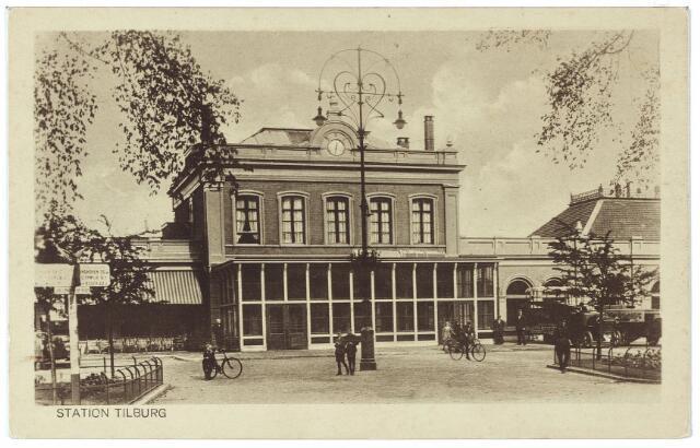 002262 - Station aan de Spoorlaan. Voor het station een fraaie twee-armige lantaarnpaal in Jugendstil. Met deze kaart kondigde Louis van den Boer, sigarenfabrikant te Tilburg, zijn komst aan bij zijn klanten in de hoop hen 'in den besten welstand aan te treffen'.