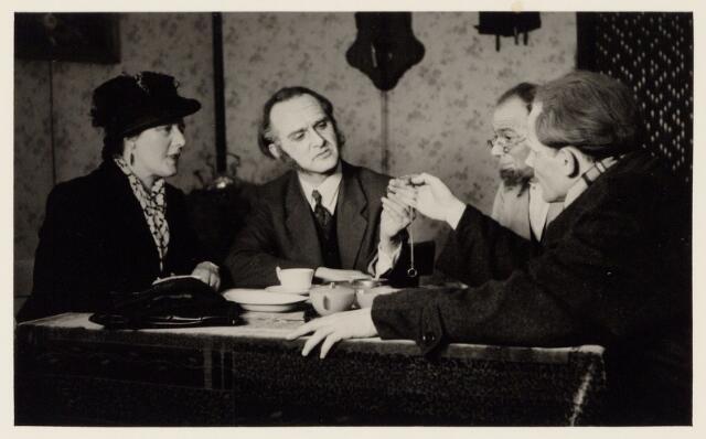 104116 - Scene uit het toneelspel Ín het nestje van de antiquair' opgevoerd op 9 april 1953 door leden van de secretarie S.V. afd. toneel. vlnr: Lucie den ouden, Louis de Cock, Kees Bertens, Jan Bierens.