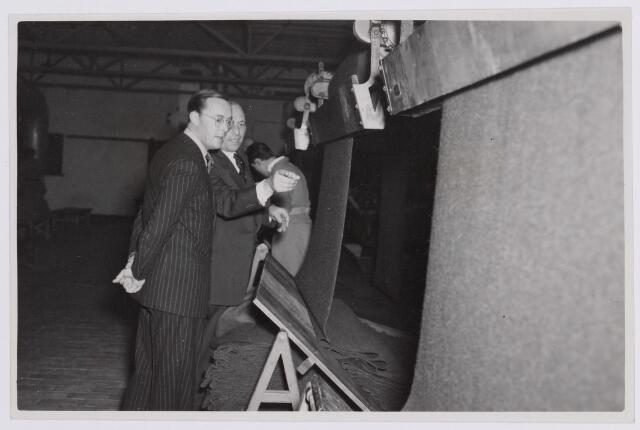 037667 - Textielindustrie. Prins Bernhard wordt door directeur Enneking van wollenstoffenfabriek H. F. C. Enneking rondgeleid tijdens diens bezoek aan de fabriek op 13 november 1950. Hier zijn ze in de droogappretuur