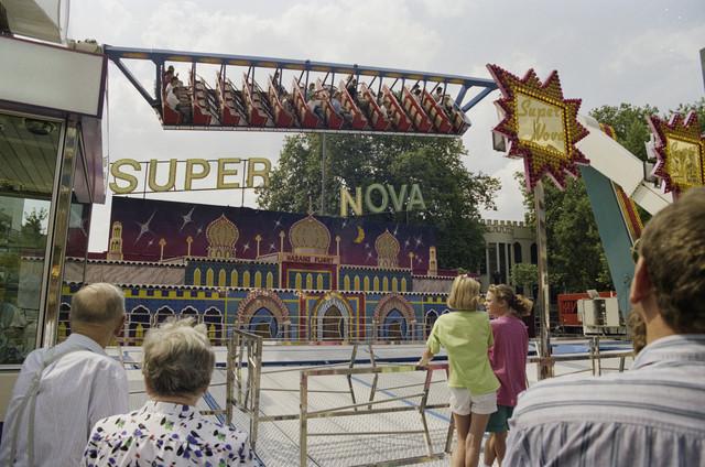 TLB023000068_002 - Attractie Super Nova met bezoekers op de kermis. De Tilburgse Kermis is de grootste kermis in de Benelux. Er staan jaarlijks tussen de 230 en 240 attracties uit binnen- en buitenland, in een 4,5 kilometer lang lint door het centrum van de stad. De kermis trekt jaarlijks meer dan een miljoen bezoekers en is daarmee een van de best bezochte evenementen van Nederland.
