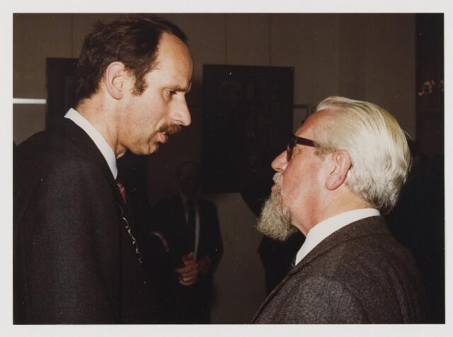 080042 - 16 april 1982 Benoeming van H.J.M. Tops als burgemeester van Udenhout. De felicitaties voor de nieuwe burgemeester hier in gesprek met pater Monaldus van den Broek, pastor van Biezenmortel
