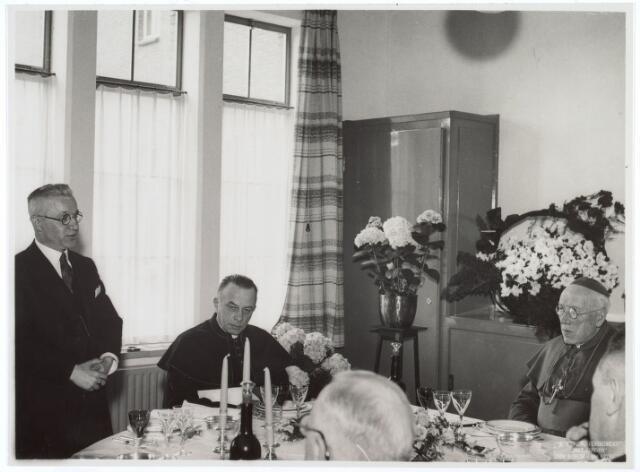 016495 - Wethouders Eijkemans spreekt de aanwezigen toe bij aanvang van het diner ter gelegenheid van de oficiële inzegening van klooster Mariahof van de Broeders Penitenten. Naast hem vicaris-genaraal Hendriks en uiterst rechts mgr. Diepen