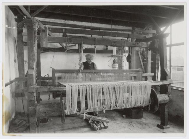 037462 - Textielnijverheid. Thuiswever Frans van Geloven aan het werk achter zijn getouw in de Tongerlose Hoefstraat 18.