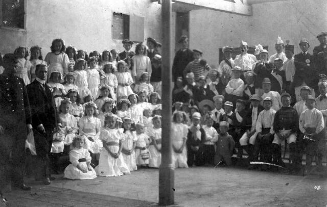 064718 - Kinderen in een fabriekshal, waarschijnlijk om deel te nemen aan een optocht. Mogelijk een Oranjefeest.