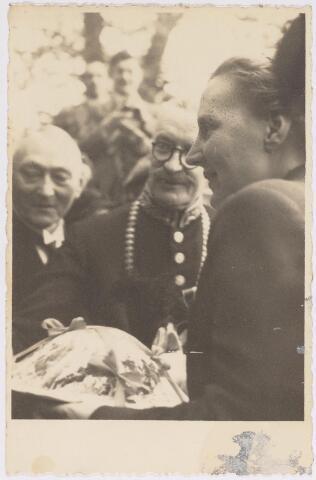042784 - Koninklijke Bezoeken. H.K.H. prinses Juliana ontvangt een cake van leerlingen van de Huishoudschool tijdens haar bezoek aan de stad de nationale feestdag, de eerste na de bevrijding. Links van haar burgemeester Van De Mortel en daarnaast gemeentesecretaris W.J. van Dusseldorp.