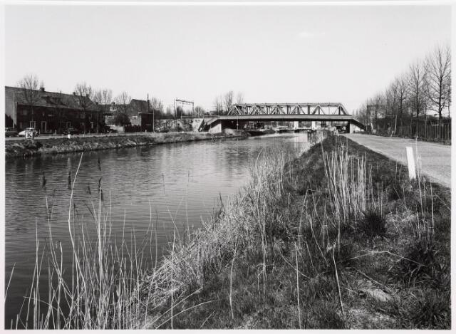 034830 - Spoorbrug over het Wilhelminakanaal. Rechts van de Hoevense Kanaaldijk het terrein van voetbalvereniging LONGA. Op de achtergrond de hefbrug aan de Bosscheweg