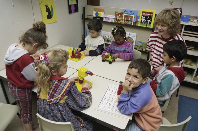 TLB023000258_002 - Kleuteronderwijzeres met kinderen in een klaslokaal, bezig met Nopper constructiespeelgoed. Dit type speelgoed werd gebruikt voor de motorische- en kleurenontwikkeling ook wel fijne motoriek genoemd.