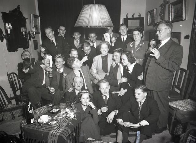 654934 - Groepsfoto. Studenten en hun ouders tijdens een feestelijke huiskamerbijeenkomst