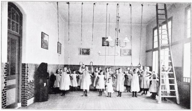 051083 - Jeugdzorg. Sport. Het gymnastieklokaal van het St.Jozefhuis-St.Anna. De kinderen aan de ringen.
