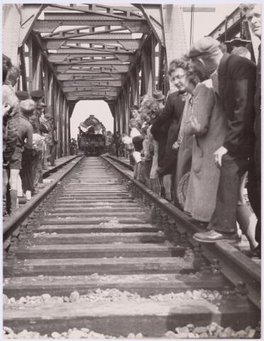 036767 - Spoorwegen, Centrale Werkplaats, Atelier, NS: Opening van de herstelde spoorbrug over het Wilhelmina kanaal met op de achtergrond een versierde locomotief van het Britse leger in november 1944.