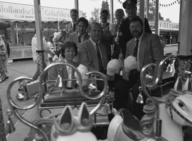 TLB023000193_001 - Het kermisprojectteam geniet na een lange voorbereidingsperiode van een suikerspin. Het team bestaat uit: 1e rij v.l.n.r. H. Willems, E. Tulfer en J. Feldbrugge (projectleider), 2e rij v.l.n.r. C. Loing en Wijkagent J. van den Nobelen, 3e rij v.l.n.r. F. van Spaandonk, A. Vialle en P. Donkers. Foto is gemaakt op de kermis in Berkel-Enschot