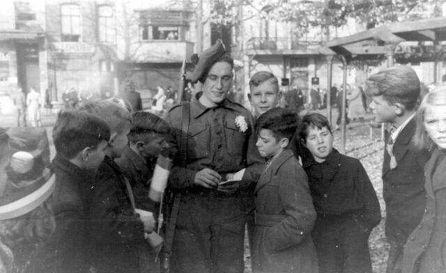 064678 - Tweede Wereldoorlog. Een bevrijder van Tilburg op de Heuvel omringd door de schooljeugd.