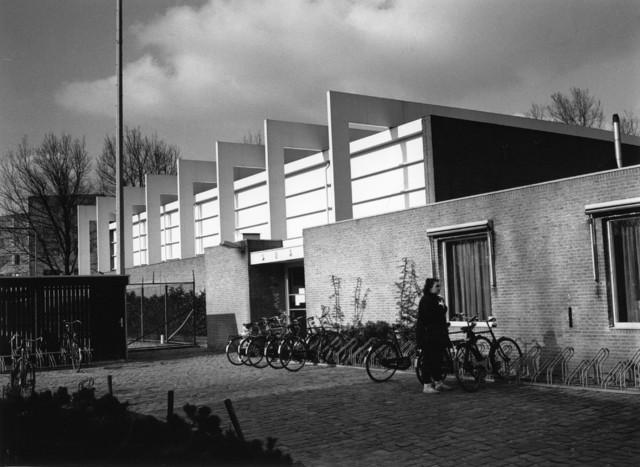 1238_F0182 - Vrouw bij een fietsenrek bij de sporthal voor studenten van de Universiteit Tilburg