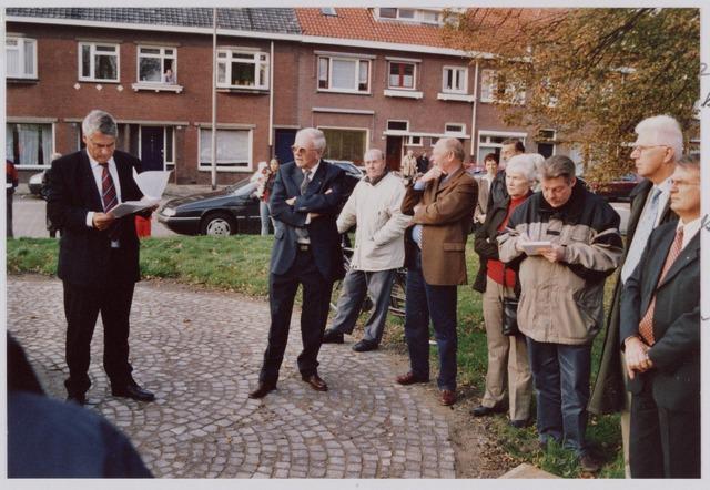 050099 - Volt, Algemeen, Kunstwerken, Onthulling, Voltvonk. Stond aanvankelijk op Volt Noord. Op 30 oktober 2002 werd dit monument opnieuw onthuld op het Transvaalplein, een locatie dicht bij het oude Voltterrein. Burgemeester J. Stekelenburg tijdens zijn toespraak. Naast de burgemeester zien we achtereenvolgens een aantal oud directeuren van Volt t.w.: 1 met zonnebril Ir. W.Hoogenboezem, 3  met bruine colbert, Ir. J. Iding met naast zich zijn echtgenote. Rechts met witte haardos Ir.Huygen, oud directeur van K.M.T., een voortzetting van Metaalwaren Volt en een van de drijvende krachten voor de verplaatsing van de Voltvonk. Dan uiterst rechts Ir. A.Daniëls de voorlaatste directeur van Volt. Met witte jas tussen Hoogenboezem en Iding is Jac de Rooij, lange tijd werkzaam geweest op de postkamer van Volt.